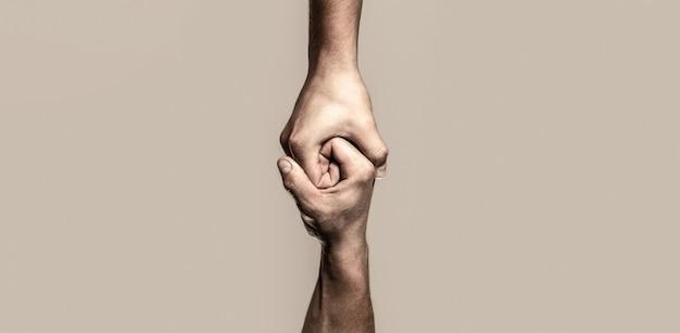 Mão amiga estendida, braço isolado, salvação. feche a mão de ajuda. conceito de mão amiga e dia internacional da paz, apoio. duas mãos, ajudando o braço de um amigo, trabalho em equipe. preto e branco.