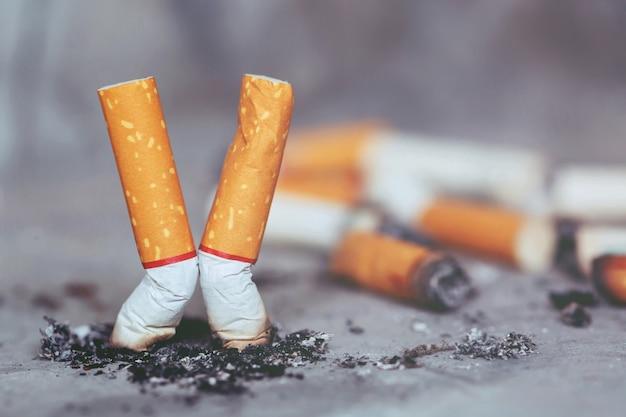 Mão apagando um cigarro, bituca de cigarro no chão de concreto, cimento nu.