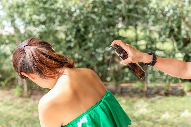 Mão aplicada proteção solar no cuidado da pele do ombro.