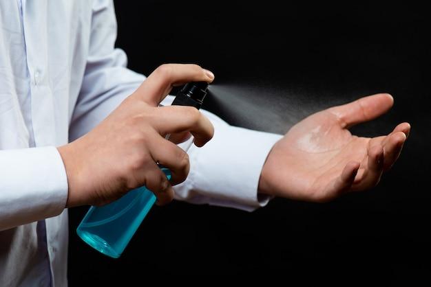 Mão aplicando álcool ou spray antibacteriano para evitar a propagação de germes, bactérias e vírus. higiene pessoal. conceito de desinfecção covid-19 coronavirus