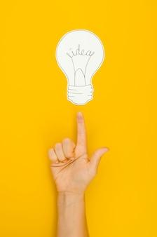 Mão apontando para uma lâmpada acender