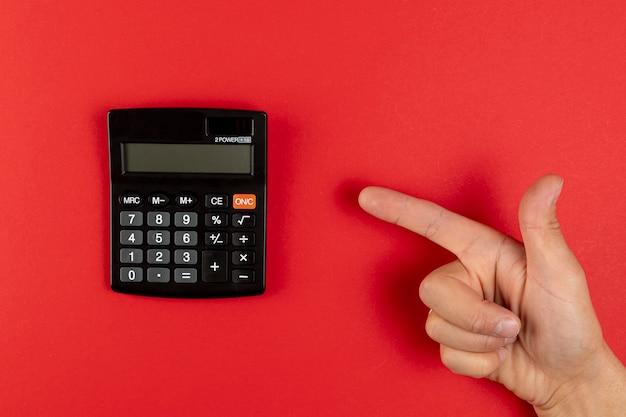 Mão apontando para uma mini calculadora