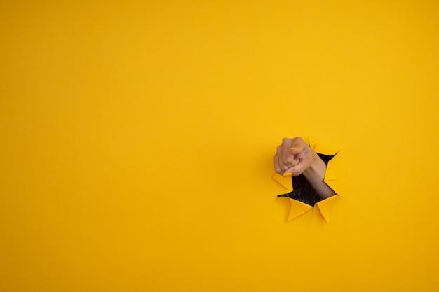 Mão apontar para a câmera de um buraco no papel amarelo rasgado.