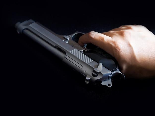 Mão, arma e gatilho com o dedo