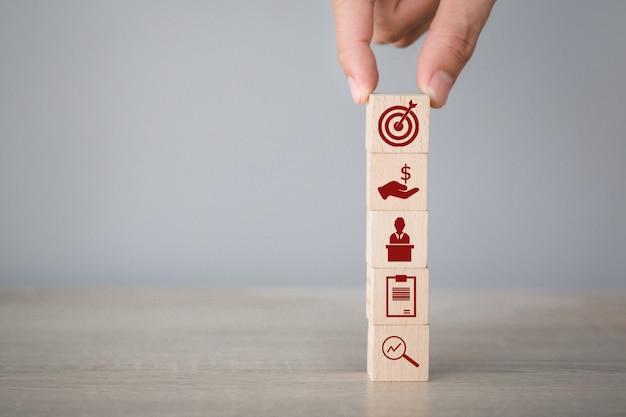 Mão arranjar bloco de empilhamento de madeira com ícone de seta e negócios, visando o conceito de negócio.