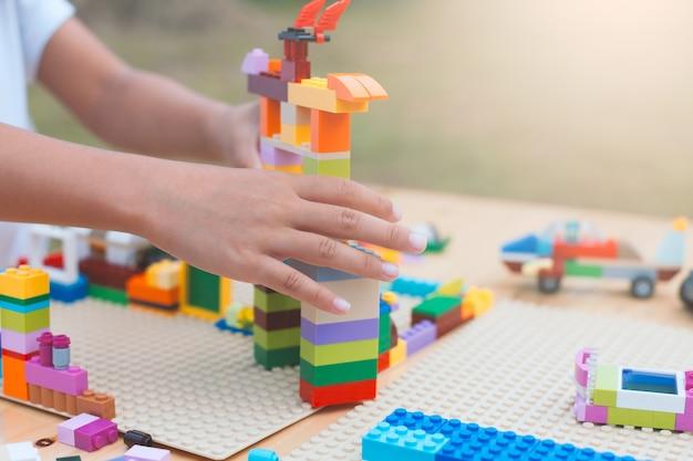 Mão asiática da menina da criança pequena que joga com blocos coloridos.
