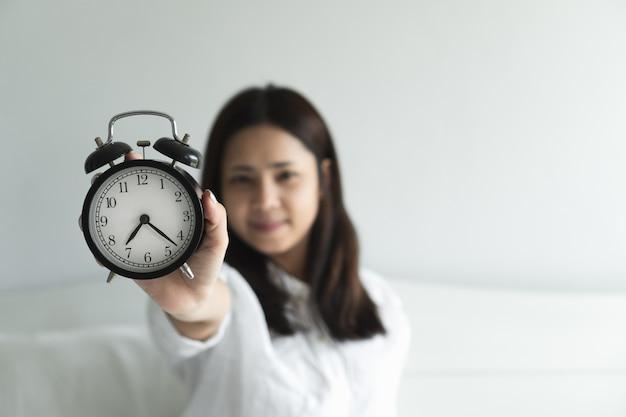 Mão asiática feliz nova da mulher que aumenta o despertador preto que aprecia acordar no amanhecer.