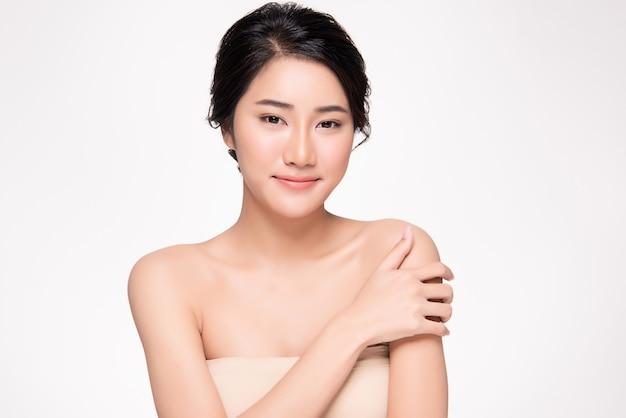Mão asiática nova bonita da mulher que toca no ombro que sente tão feliz e alegre. pele limpa e fresca, isolada no branco, cosmetologia de beleza