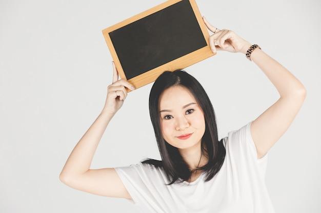Mão asiática nova que guarda a placa preta com copyspace no cinza.