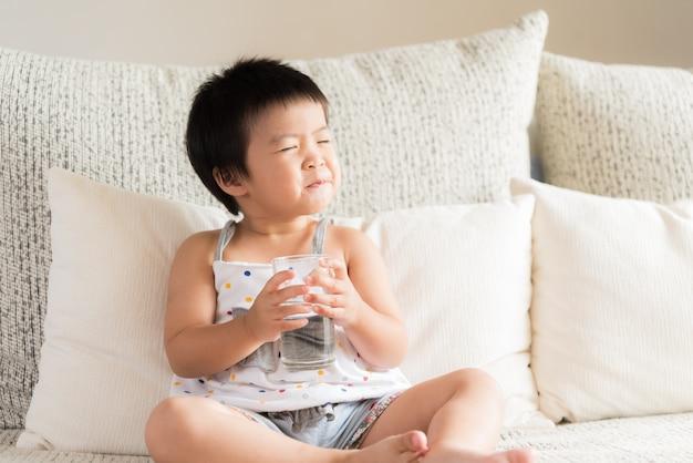 Mão asiática pequena feliz da menina que guarda o vidro de água potável e o riso, sentando-se no sofá