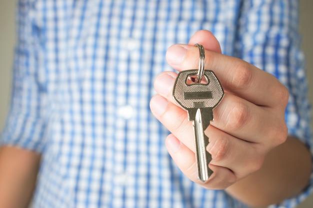 Mão asiática segurando a chave da casa