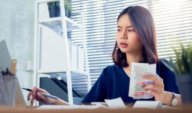 Mão asiática triste da mulher que guarda a conta da despesa e o cálculo sobre as contas da dívida mensalmente na tabela no escritório em casa.