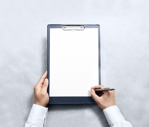 Mão assinando a área de transferência em branco com papel a4 branco