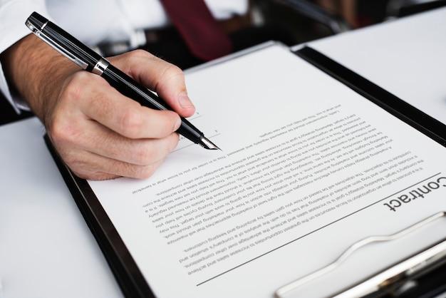 Mão assinando contrato de negócios