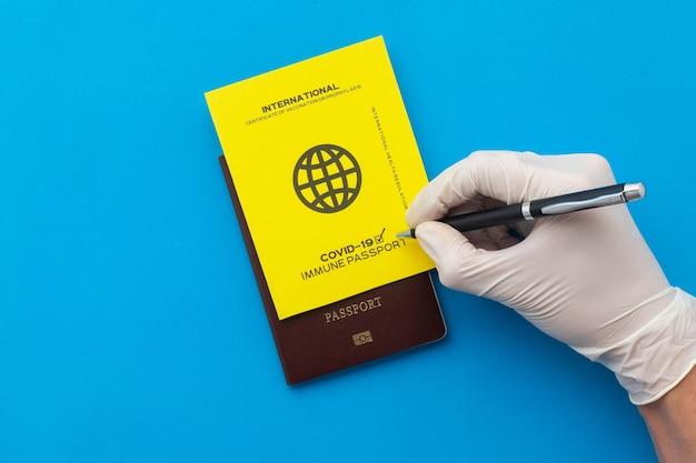 Mão assinando passaportes de vacina como prova de que o titular foi vacinado contra covid-19