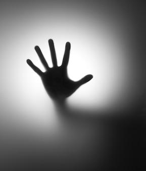 Mão atrás de um vidro fosco