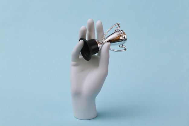 Mão branca de um manequim segura a taça do campeonato em um fundo azul. esporte, conceito de campeão.