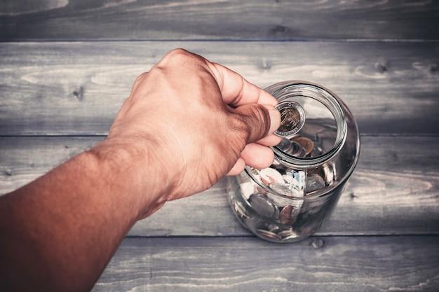 Mão cai dinheiro em um frasco de vidro para uma poupança
