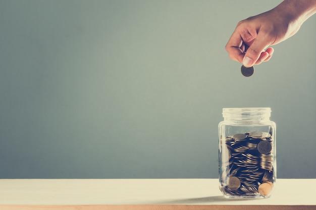 Mão cai dinheiro em uma garrafa de vidro, conceito de poupança