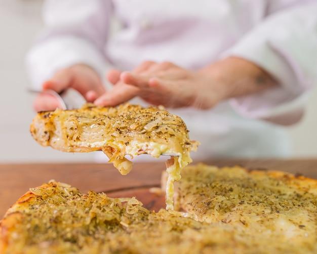 Mão cheff feminina com uma fatia de pizza de cebola