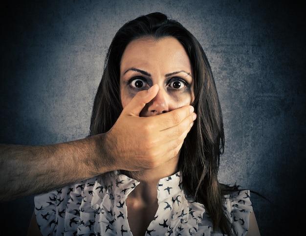 Mão cobrindo a boca de uma menina ferida e assustada