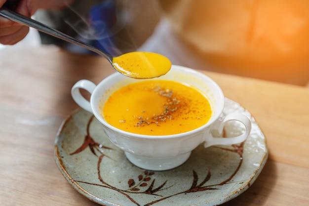 Mão colhendo sopa de abóbora pureed clássico com vapor e cobertura com pimenta. servido em copo cerâmico na mesa de madeira.