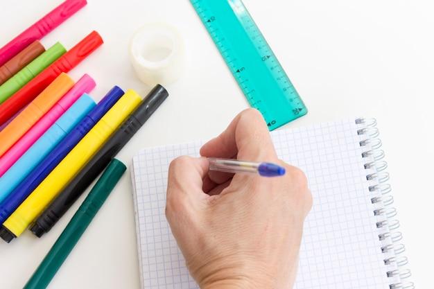 Mão colhida escrevendo no caderno. multi canetas de marcador coloridas, caderno, régua no branco.
