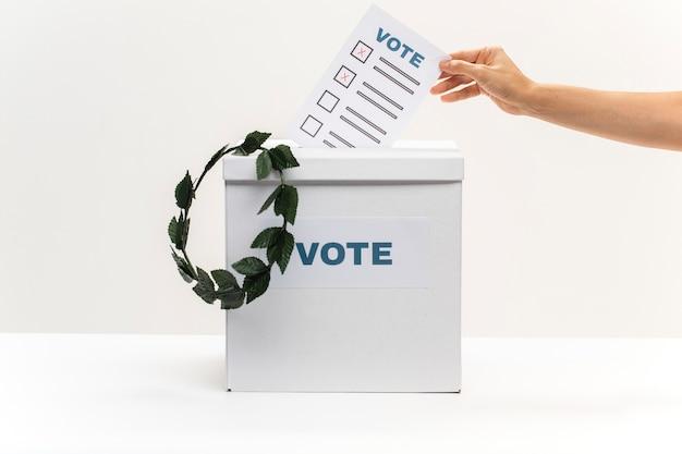 Mão coloca boletim de voto na caixa de votação e uma coroa