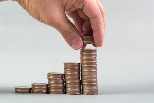 Mão coloca moedas de dinheiro para a pilha de moedas