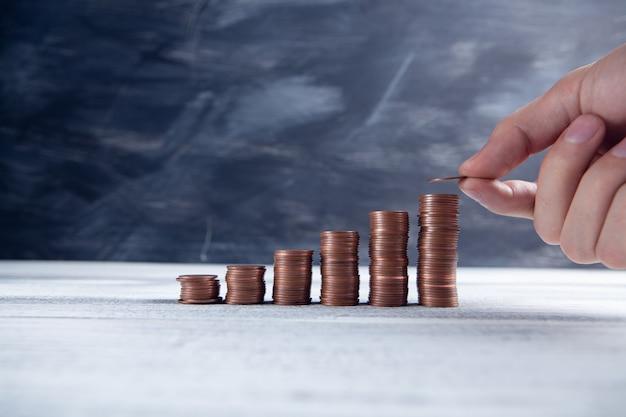 Mão coloca moedas na forma de um gráfico crescente