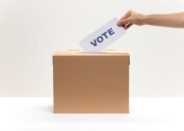Mão coloca o boletim de voto na caixa de votação