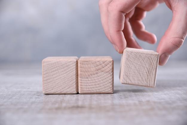 Mão coloca o cubo de madeira em branco em cima da mesa