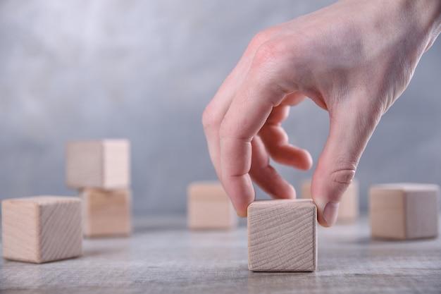 Mão coloca um cubo de madeira em branco, com espaço para sua palavra, letra, símbolo em cima da mesa. lugar para texto, espaço para cópia livre