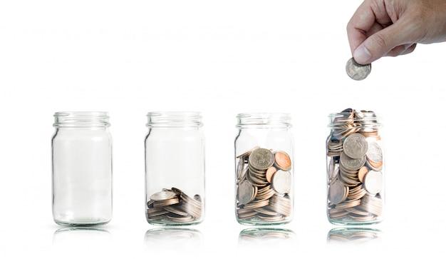 Mão, colocando a moeda no pote para economia e investimento.