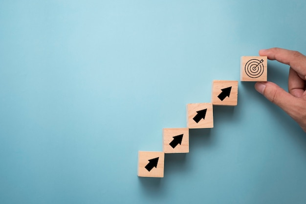 Mão, colocando a placa de alvo virtual e seta que imprime a tela no cubo de madeira. objetivo de realização de negócios e conceito de objetivo objetivo.