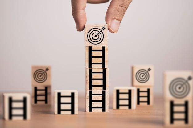 Mão, colocando a placa de destino no topo da escada que imprime a tela em um bloco de cubo de madeira, configure o objetivo de realização do desafio no conceito de negócios e vida.