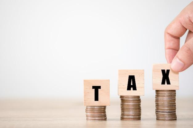 Mão, colocando a redação de imposto que é impressa a tela para cubos de madeira no empilhamento de moedas. conceito crescente de impostos e iva.
