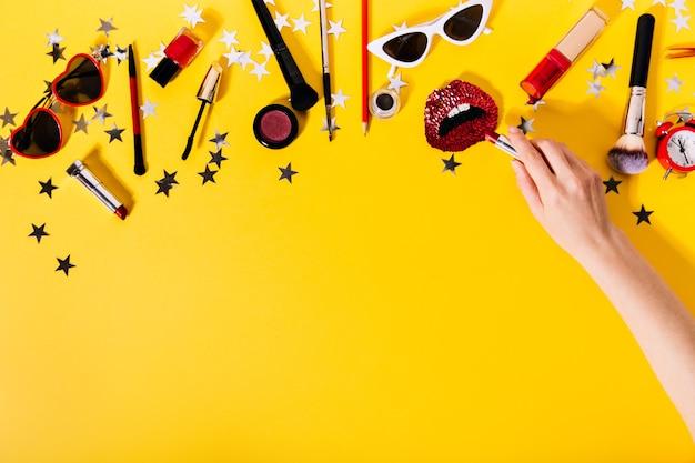 Mão colocando batom no broche vermelho em forma de lábios contra um conjunto de cosméticos.