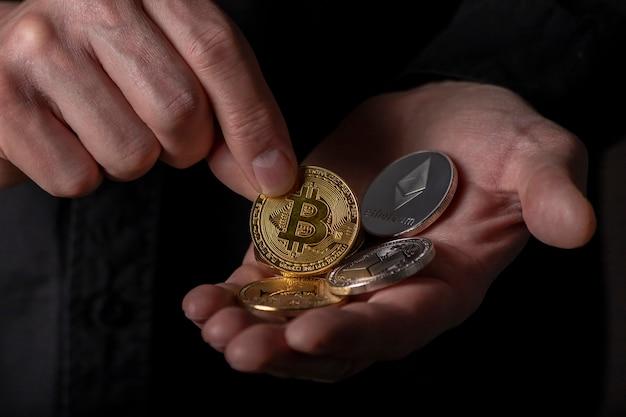 Mão colocando bitcoin dourado na palma da mão com outra criptomoeda na mão masculina sobre fundo preto ...