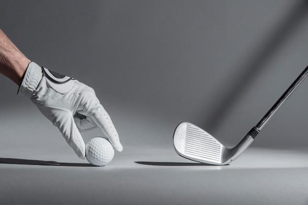 Mão colocando bola de golfe