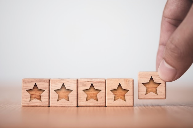 Mão colocando cinco estrelas esculpidas em um cubo de madeira.