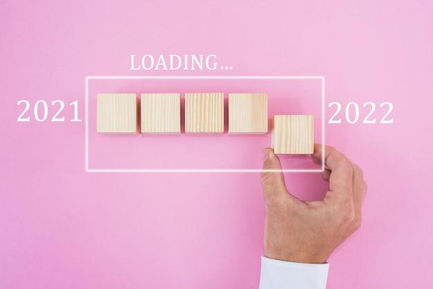 Mão colocando cubo de madeira para contagem regressiva até 2022. carregamento do ano de 2021 a 2022. conceito inicial