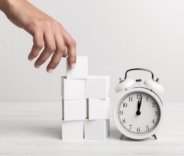 Mão colocando cubos brancos ao lado de um relógio