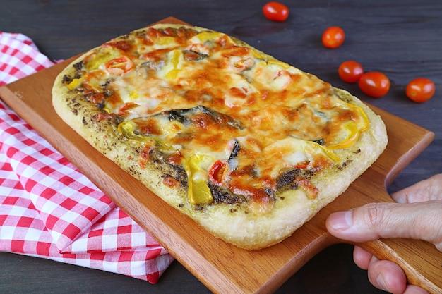 Mão colocando deliciosa pizza pesto de vegetais caseiros recém-assados na mesa