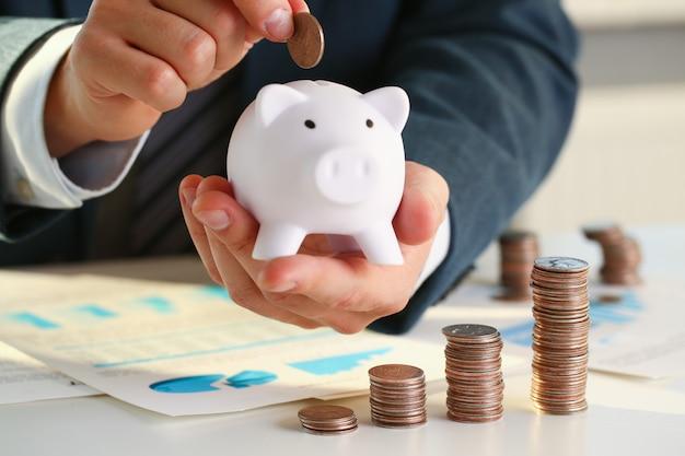 Mão colocando dinheiro no porco