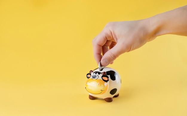 Mão colocando duas moedas de euros em um cofrinho em forma de uma vaca fofa