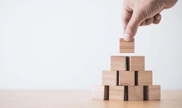 Mão, colocando e empilhando cubos de madeira em branco na mesa com espaço de cópia para o texto de entrada e o ícone do infográfico.