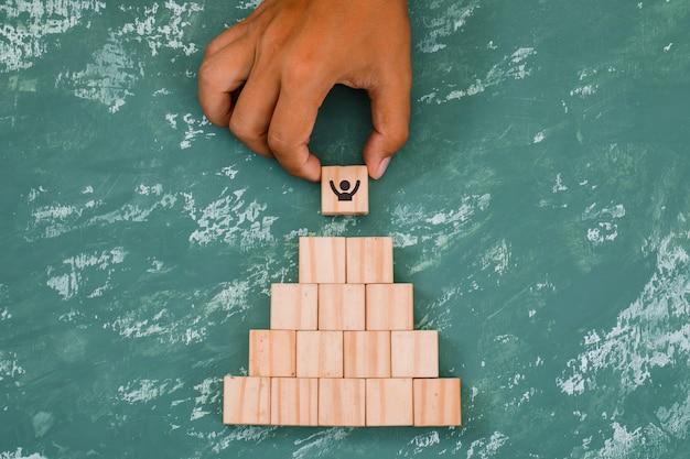 Mão colocando e empilhando cubos de madeira