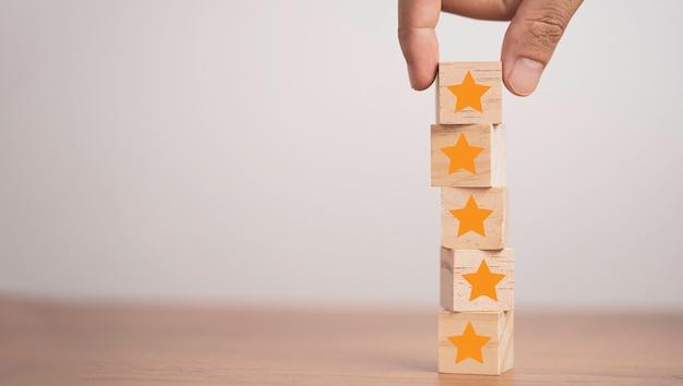 Mão colocando estrelas amarelas que imprimem a tela em um bloco de cubo de madeira para o conceito de satisfação do cliente.