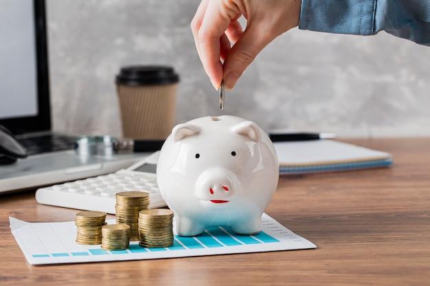 Mão colocando moeda no cofrinho e gráfico de crescimento